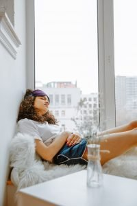 girl sitting in a window in pyjamas holding her tummy and wearing an eye mask